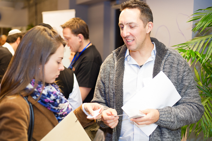 A recent immigrant to Israel exchanges business cards with the QA Manager of Pontis Israel, at a Job Fair focusing on SaaS companies and held at Google TLV Campus.