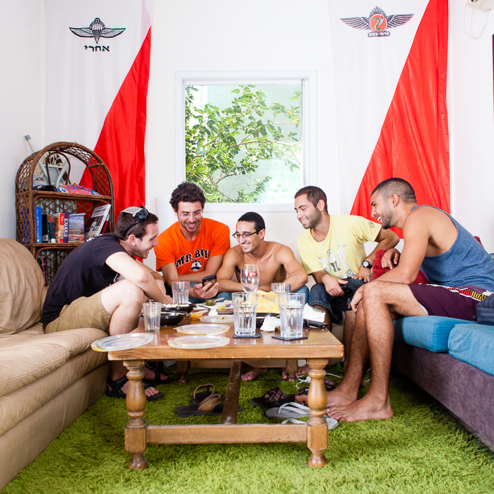 Friday morning. Alex enjoys shwarma at home with friends from his unit before heading to the beach.